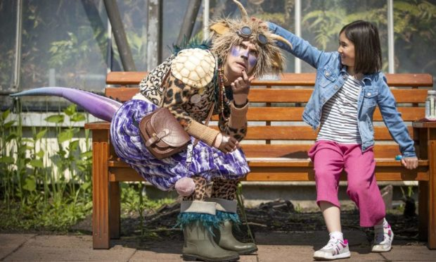 """Lilia Barbirou, aged eight, meets """"The Undiscovered Creature"""" during a performance in the Royal Botanic Garden Edinburgh."""