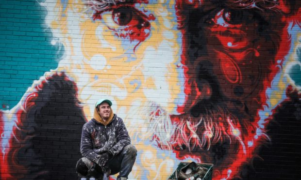 Michael Corr with his mural of Michael Marra for the Love Lochee street art project. Picture: Mhairi Edwards/DCT