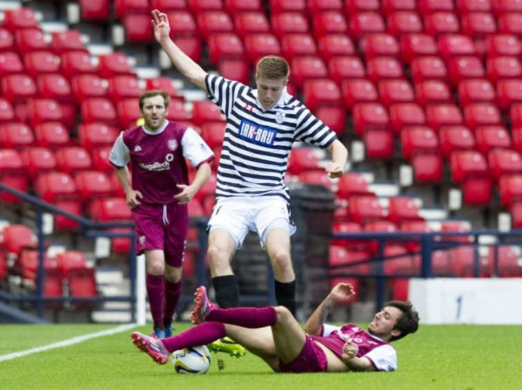 Shaun Rooney being tackled by Arbroath's Dylan Carreiro.