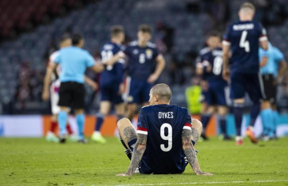 Scotland striker Lyndon Dykes sits dejected on the Hampden turf after the defeat to Croatia.