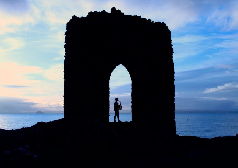 David Behrens playing the saxophone at Lady's Tower near Elie.