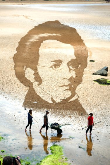A mural of composer Schubert drawn on the sand at a Fife beach