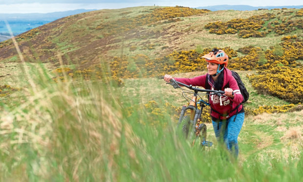 Gayle pushing her bike up a steep section of the Hill of Alyth.