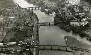 Photo shows aerial view of Perth taken above the River Tay in 1959, facing north with the Ferguson Gallery and rail bridge in the foreground and Smeaton's Bridge in the background.