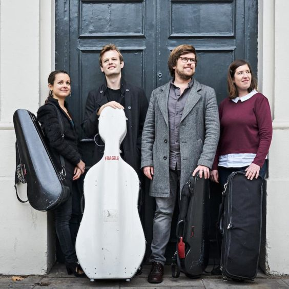 The band The Castalian Quartet posing with their instruments in front of a black door