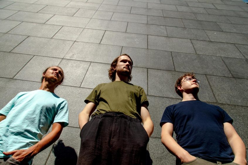 The band The Fergus McCreadie Trio posing in front of a stone wall