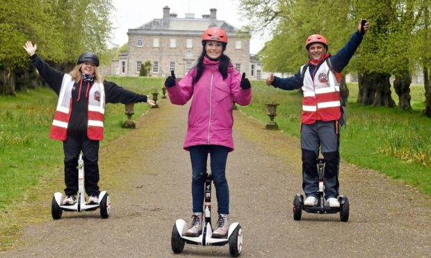 Gayle joins a Segway tour Haddo Country Park run by Wheelie Fun. The picture shows Gayle flanked by company owners Claire and Merv Christie in front of Haddo House.