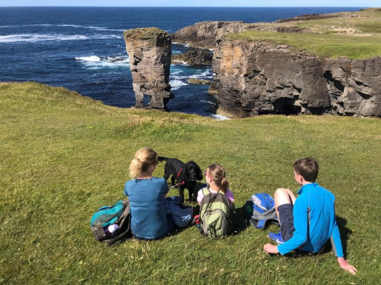 A family and a dog looking over Yesnaby Castle, Orkney