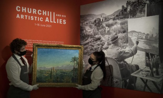Gallery assistants hold The Atlas Mountains from Marrakesh by Sir Winston Churchill, at Christie's, central London, before it's offered for sale by the auction house. Picture date: Thursday June 3, 2021. PA Photo. Photo credit should read: Kirsty O'Connor/PA Wire