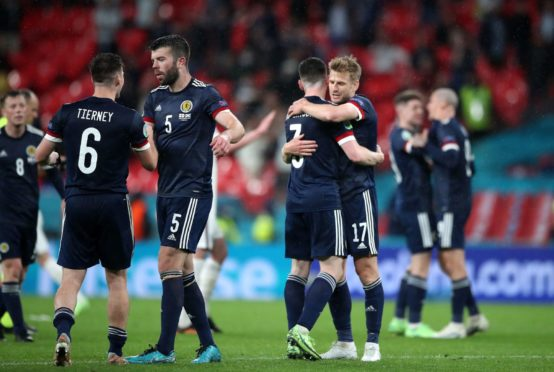 Scotland players embrace at the close of the game. Picture by PA.
