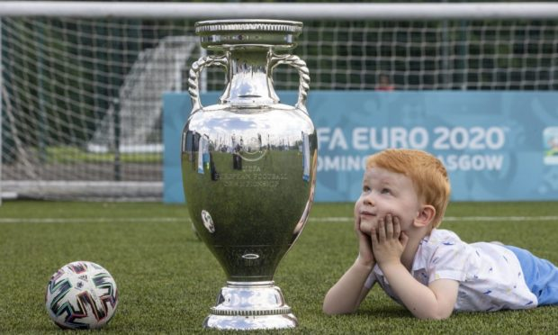 Handout photo dated 02/06/2021 provided by JSHPIX of Glasgow youngster Hugo getting their first look at Euro 2020 trophy as the Henri Delaunay Cup made a special visit to Glasgow's Walking Football programme today as part of the UEFA EURO 2020 Trophy Tour. Issue date: Wednesday June 2, 2021. PA Photo. The iconic trophy is visiting a small number of community events in the city as excitement builds ahead of Scotland's first match against the Czech Republic at Hampden Park. Photo credit should read: Jeff Holmes/PA Wire. NOTE TO EDITORS: This handout photo may only be used in for editorial reporting purposes for the contemporaneous illustration of events, things or the people in the image or facts mentioned in the caption. Reuse of the picture may require further permission from the copyright holder.