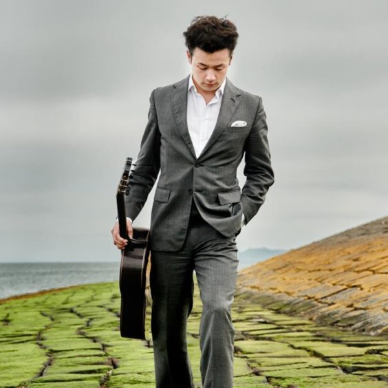 Sean Shibe wearing a suit, walking with his guitar