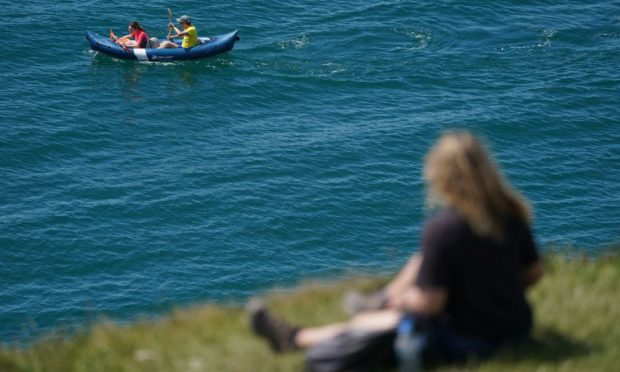 People kayak in the sea near to Durdle Door in Dorset, on the first day of meteorological summer. Picture date: Tuesday June 1, 2021. PA Photo. The UK could see record temperatures for the second day in a row after the mercury hit 25C for the warmest day of the year so far on Bank Holiday Monday. See PA story WEATHER Summer. Photo credit should read: Andrew Matthews/PA Wire