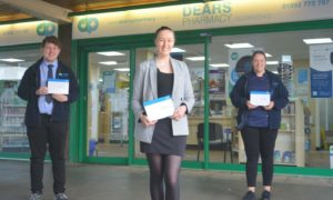 Pharmacists outside Glenrothes pharmacy where free lateral flow testing kits are available.