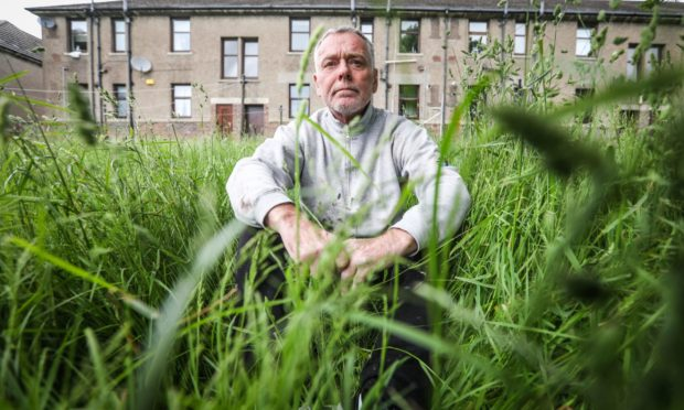 Neil McLaren sits in the overgrown grass where needles have been found.