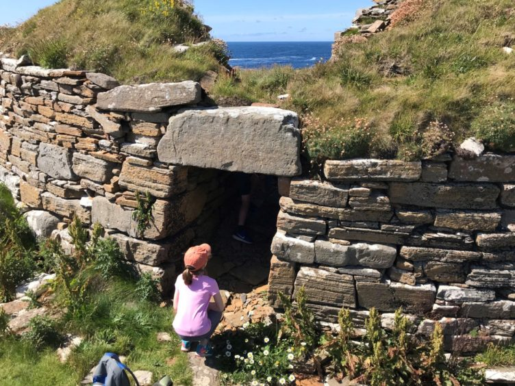 A girl looking at a cliff rock in Broch of Borwick, Orkney