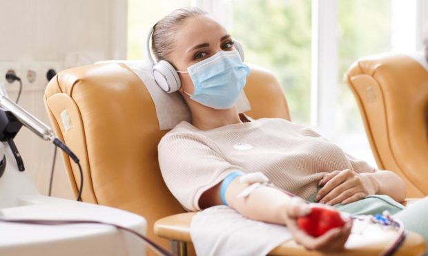 A woman lying down giving blood wearing a mask