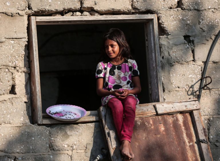 A Palestinian girl sits at the window of a house during hot weather near Khan Younis refugee camp in southern Gaza Strip, on June 29, 2021.