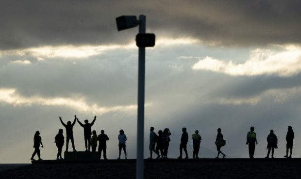 People along Irvine Harbour wall listen to music from one of the speakers on Irvine Beach, on the Ayrshire coast, at the launch the UK premiere of the new public sound installation Signal-On-Sea. Jane Barlow/PA Wire