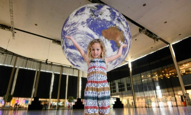 EDITORIAL USE ONLY Amelie, aged 5, in front of the art installation entitled 'Gaia' by Luke Jerram, as it goes on display at centre:mk as part of IF: Milton Keynes International Festival. Picture date: Friday July 9, 2021. PA Photo. Gaia measures 7m in diameter and features highly detailed NASA imagery of the Earth's surface. It is one of 3 pieces to go on display at the shopping centre, which will also feature 'Arrivals + Departures' by Yara + Davina and world premiere 'Breathing Room' by Anna Berry. The IF: Milton Keynes International Festival 2021, of which centre:mk is the headline sponsor, runs in July from Saturday 10th to Friday 30th. Photo credit should read: Jonathan Hordle/PA Wire