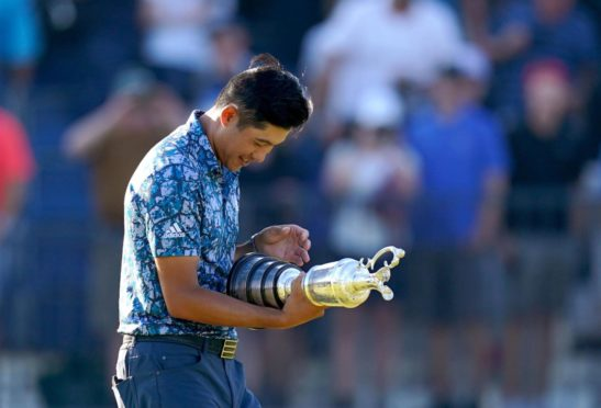 Collin Morikawa checks his name on the Claret Jug after his Open victory.