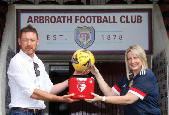Stuart McCaffrey of the Scottish Football Partnership Trust, handing over the defibrillator to Shelley Hague.