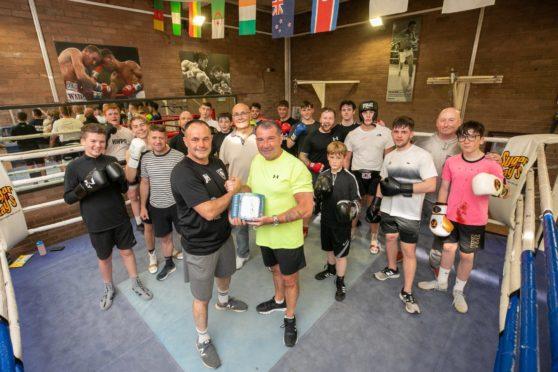 Gary Strachan hands over the defibrillator to  Lochee Boys Club.
