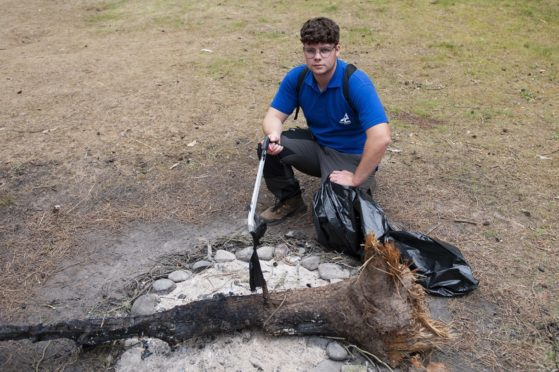 Ranger Owen Barron with one of the damaged pieces of tree.