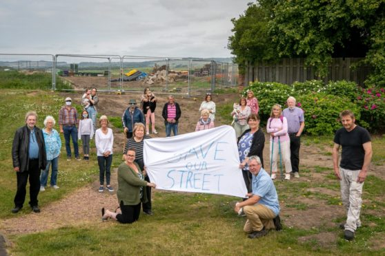 Residents gather to protest over the through road proposal.