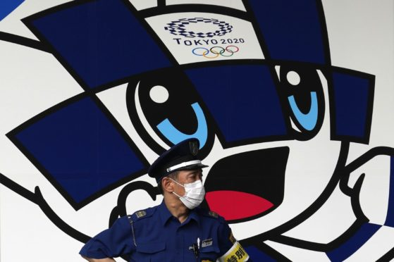 A masked security guard in front of Tokyo 2020 Olympics mascot Miraitowa.