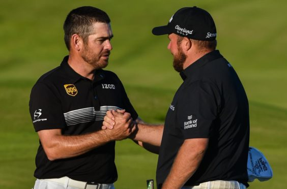 Leader Louis Oosthuizen is congratulated by defending champion Shane Lowry.