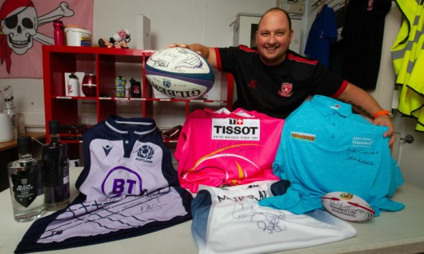 Brechin Rugby Club chairman Mike Reid with some of the lots in a silent auction being run for club funds. Pic: Paul Reid