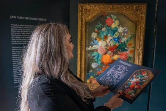 Kirsty McKay (Activity Engagement Officer PKAVS) studies the history of Jan van Huysum's magnificent painting, Flowers in a Terracotta Vase (1736–7) whilst on display at the Walled Garden in the grounds of the Murray Royal Hospital. Picture: Kenny Smith/DCT Media.