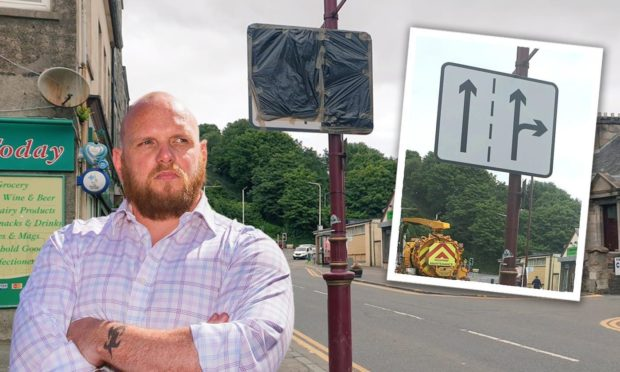 Cowdenbeath councillor Darren Watt climbed the lamp post to cover the offending road sign.