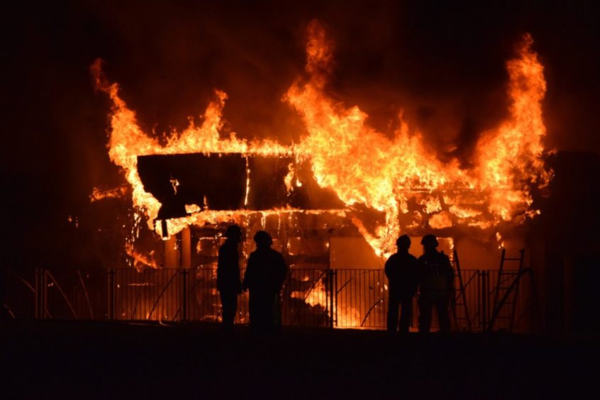 A school building on fire at night