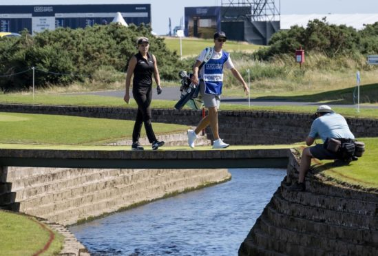 Lexi Thompson and her caddie Paul Drummond cross the Barry Burn at Carnoustie.