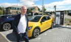 Mike Devine poses before charging his EV in Forfar