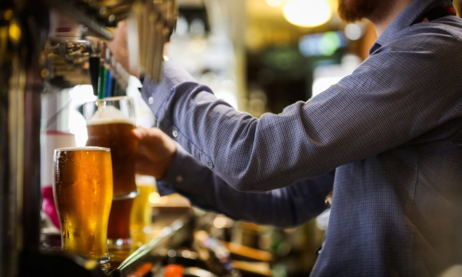 A barman pouring a pint.