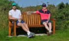 Two passing golfers resting on the Graham Proctor memorial bench at St Andrews Links