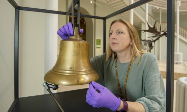 Curator Meredith Greiling with the Extinction Bell