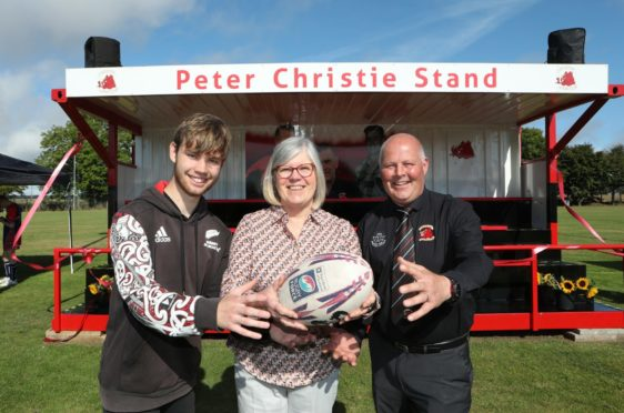 Peter Christie's wife, Heather and son Daniel, 17, at the unveiling of the new stand with Carnoustie Rugby Club president Colin Murray. Pic: Gareth Jennings/DCT Media.