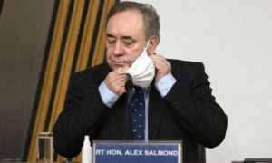 Former first minister Alex Salmond removes a face mask before giving evidence to a Scottish Parliament Harassment committee