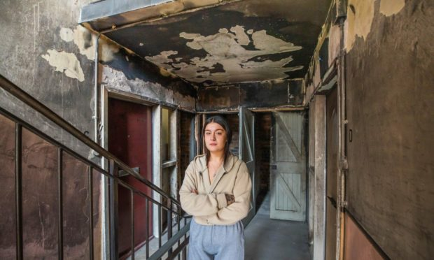 Kaylin Worsley in the fire-damaged communal close of her Aboyne Avenue home