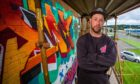 Lead artist Adam Milroy alongside examples of the graffiti art at Dunsinane House painted over the weekend.