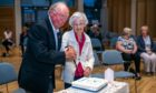 Founding figures Derick Gourlay and Margo Geddes cut the Monifieth Befrienders 21st anniversary cake. Pic: Steve Brown/DCT Media.