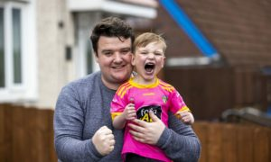 Four-year-old Daithi MacGabhann with his dad Mairtin MacGabhann at their home in Belfast. Liam McBurney/PA Wire