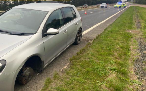 The broken down car's tyre is missing.