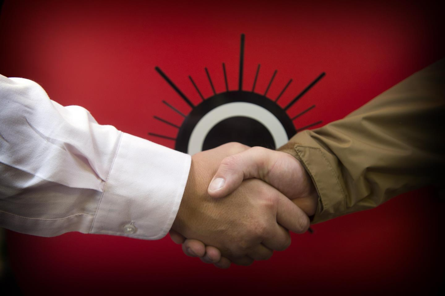 Two people shaking hands in front of the Poppyscotland logo