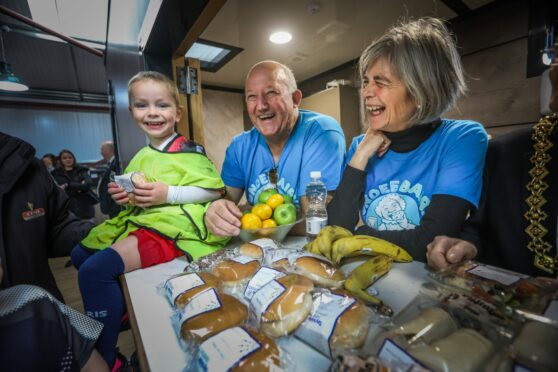 Dundee Bairns chairman David Dorward and vice-chairwoman Jacquie Roberts at a food and fun event with Caleb Sturrock.