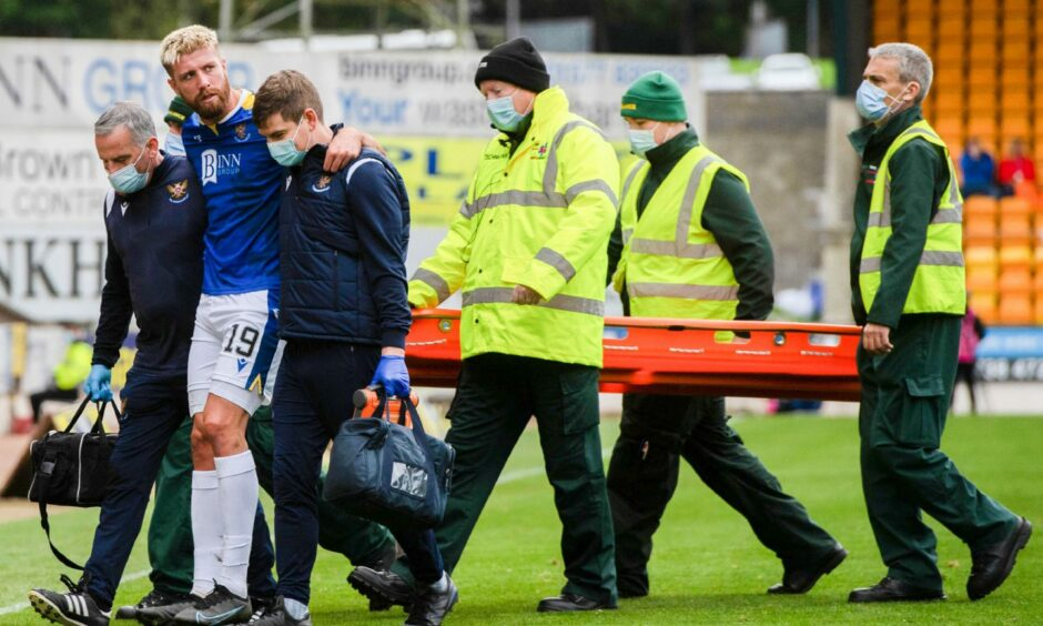 Shaun Rooney is helped from the field after picking up an ankle injury against Livingston.